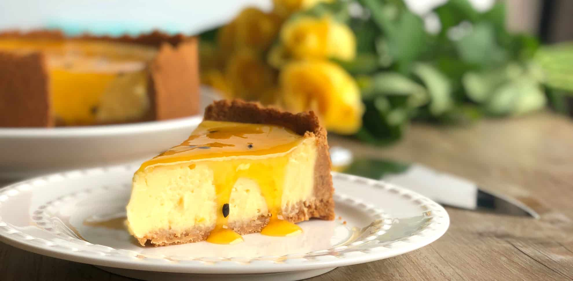 Slice of Just A Mums baked cheesecake with barkers passionfruit sauce