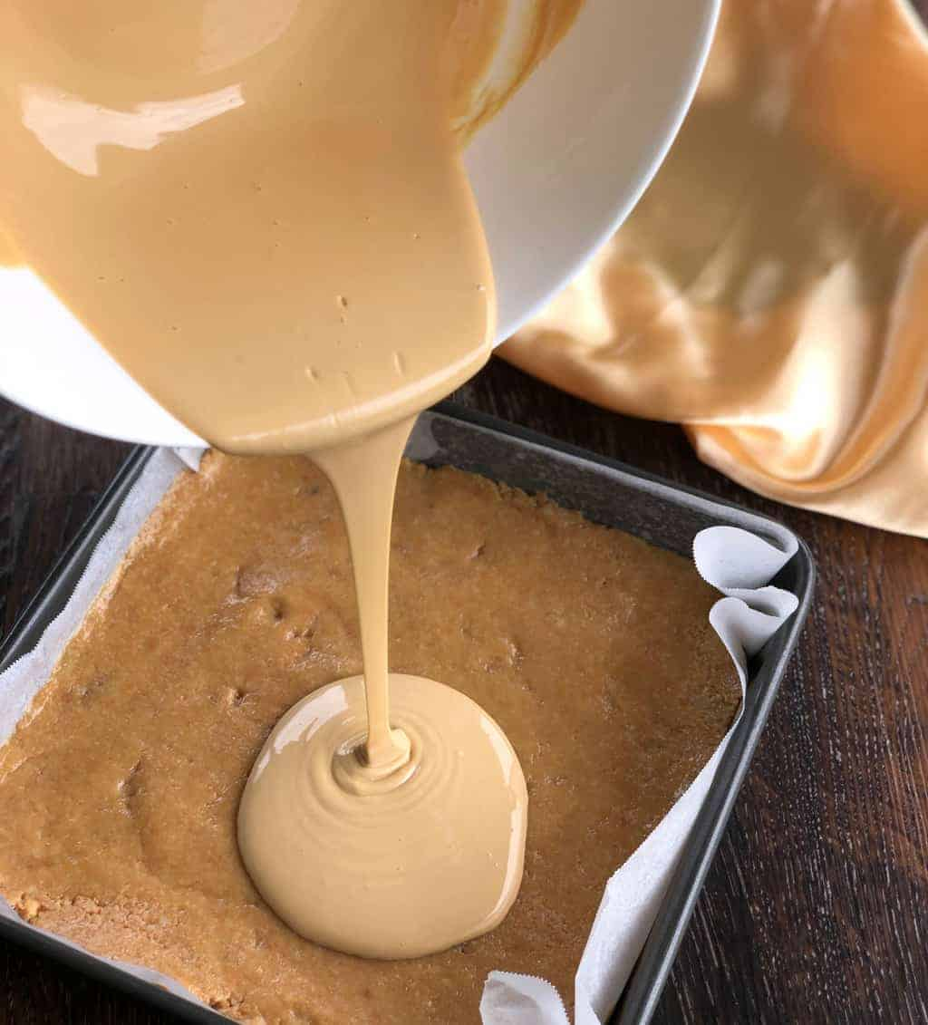 Pouring melted caramilk over a no bake slice