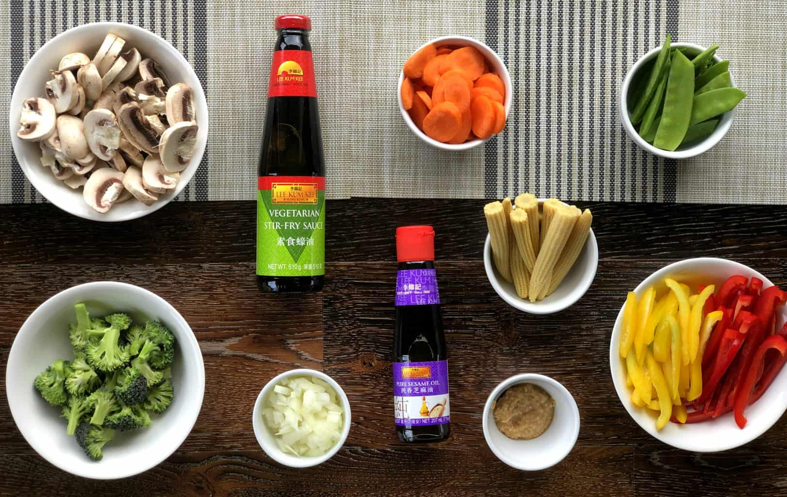 Flatlay of prepared vegetables for Vegetarian Stir Fry, mushrooms, broccoli, onion, garlic, baby corn, carrots, snow peas capsicum and two Lee Kum Kee sauces
