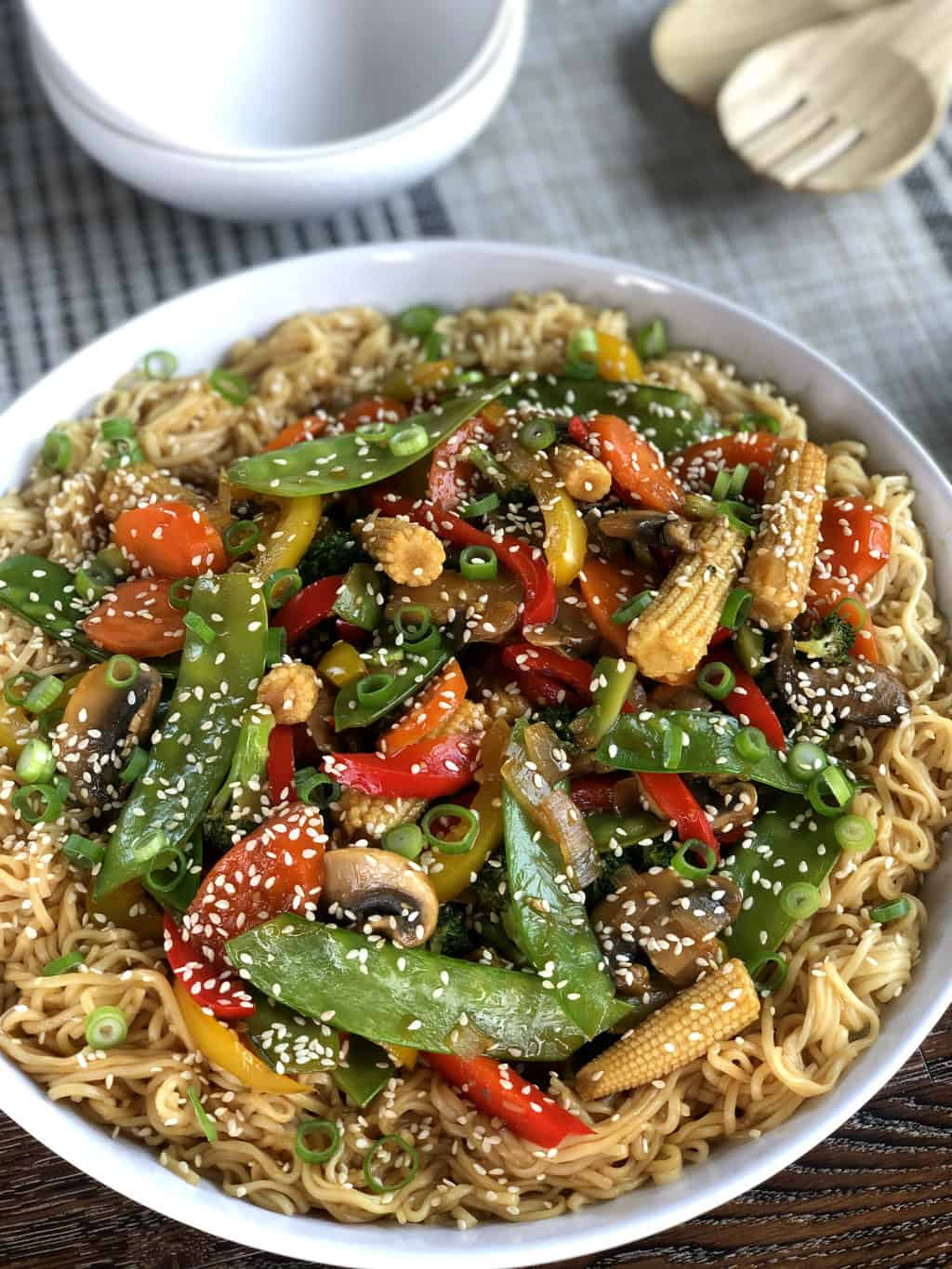 Large white serving bowl with egg noodles and vegetarian stir fried vegetables