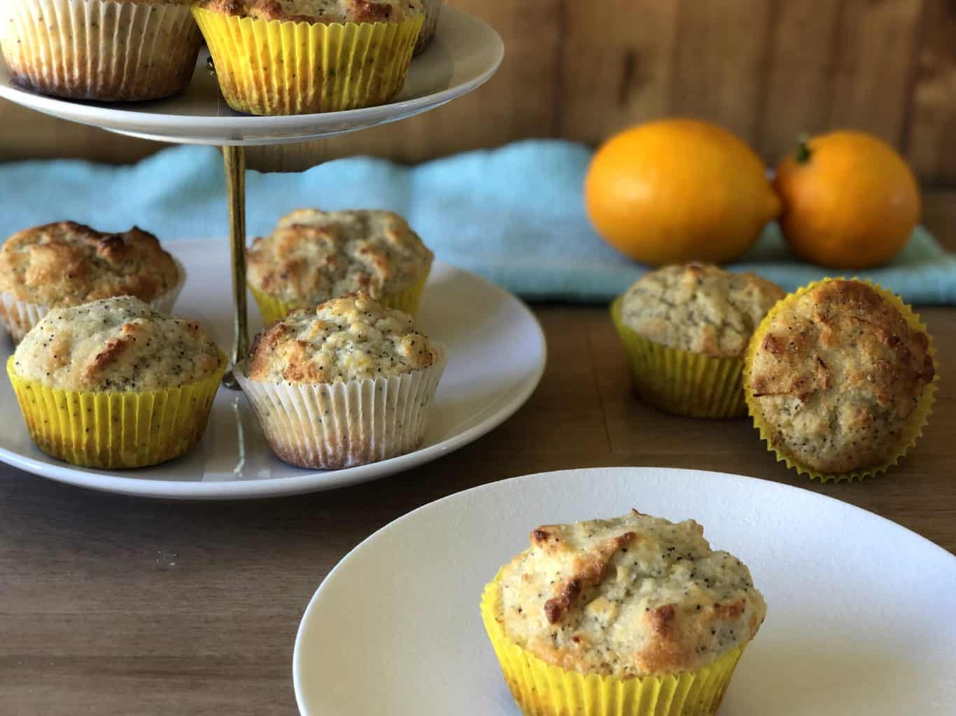 Tiered plate of lemon muffins with two fresh lemons and other muffins scattered around