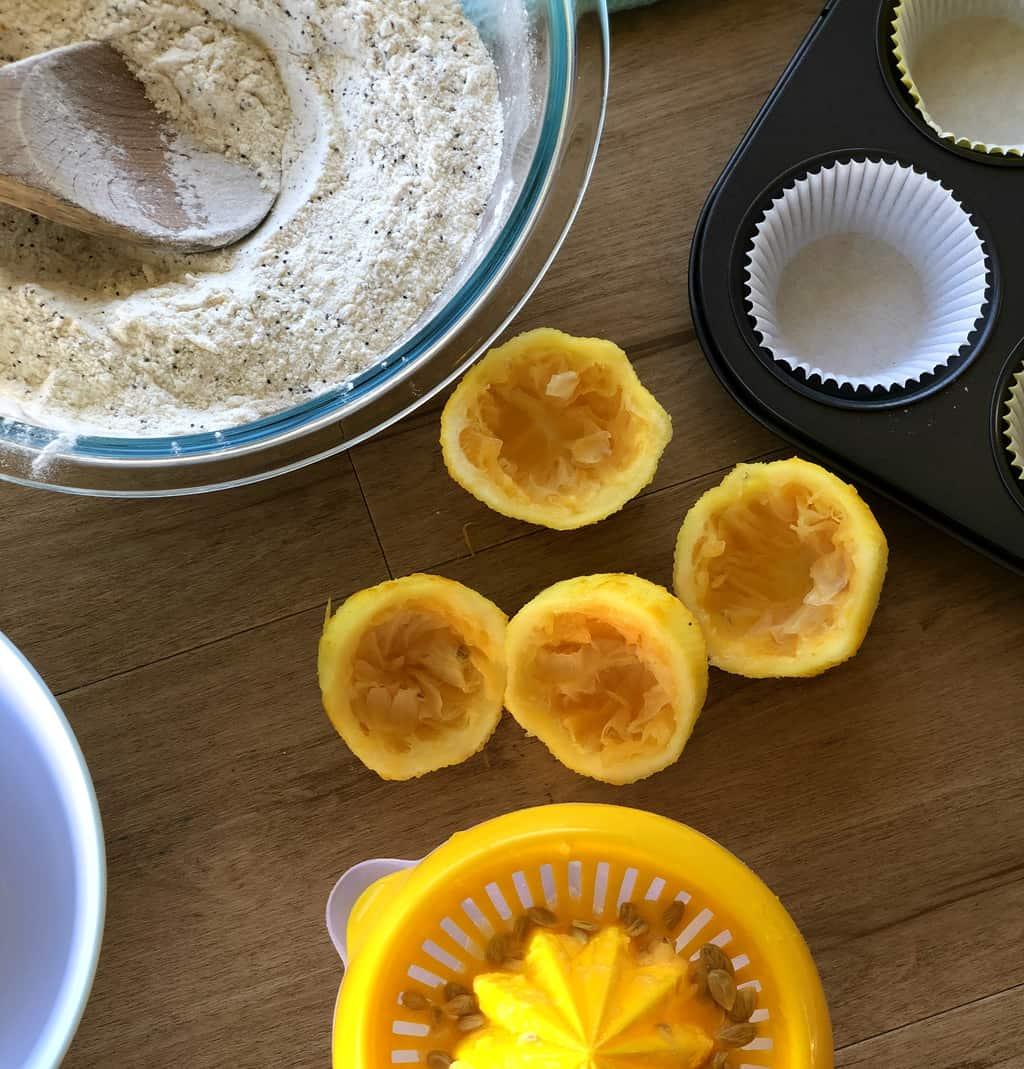Prepared dry ingredients and 4 lemon halves that have been juiced in a lemon juicer