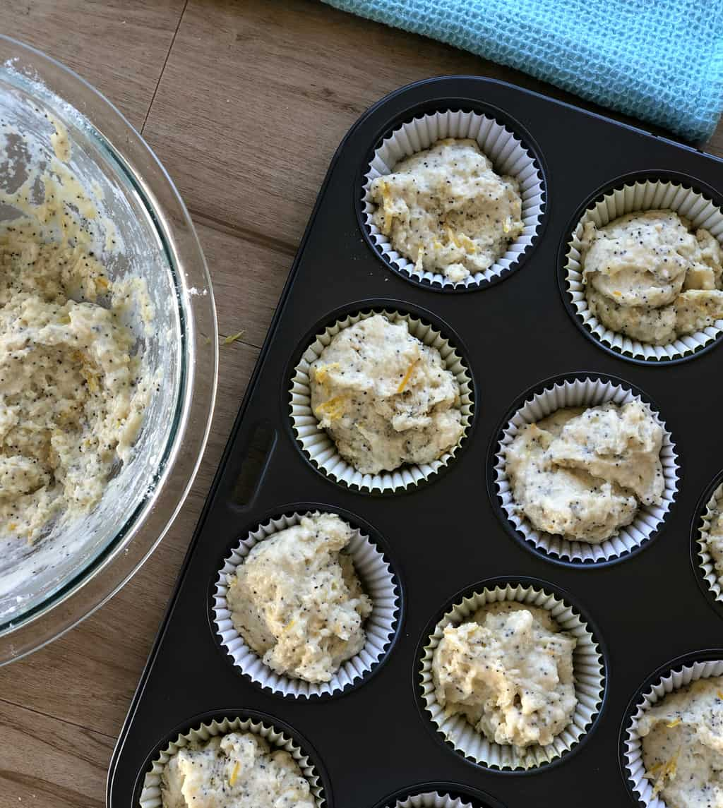 Uncooked batter for lemon and poppy seed muffins in cupcake cases in a black muffin tray.