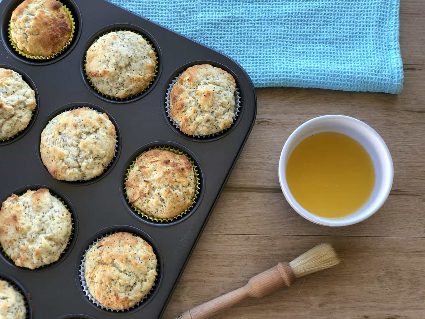 Freshly baked muffins in a muffin tin with a sugar lemon glaze prepared and a pastry brush