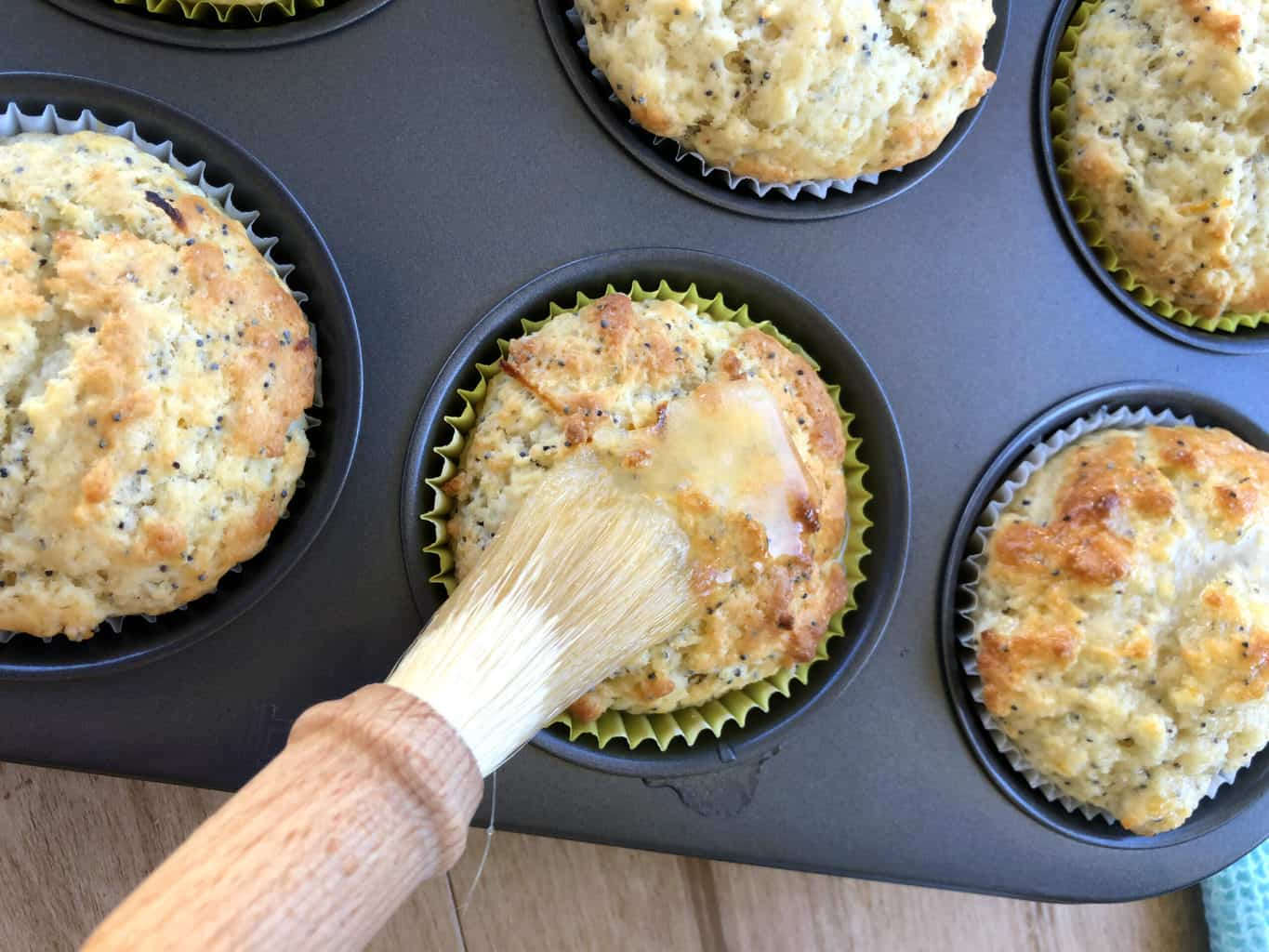 Baked muffins being spread with glaze with a pastry brush