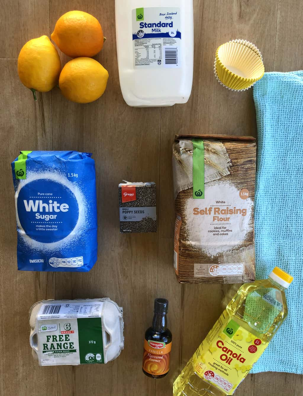 Image shows the ingredients in the lemon and poppy seed muffins, fresh lemons, milk, sugar, poppy seeds, self raising flour, oil, vanilla and eggs