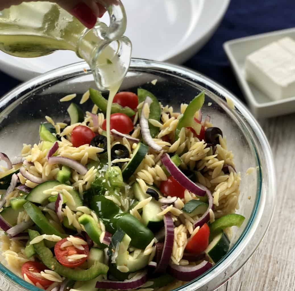 Pouring Greek Salad Dressing over a Orzo Pasta Salad.
