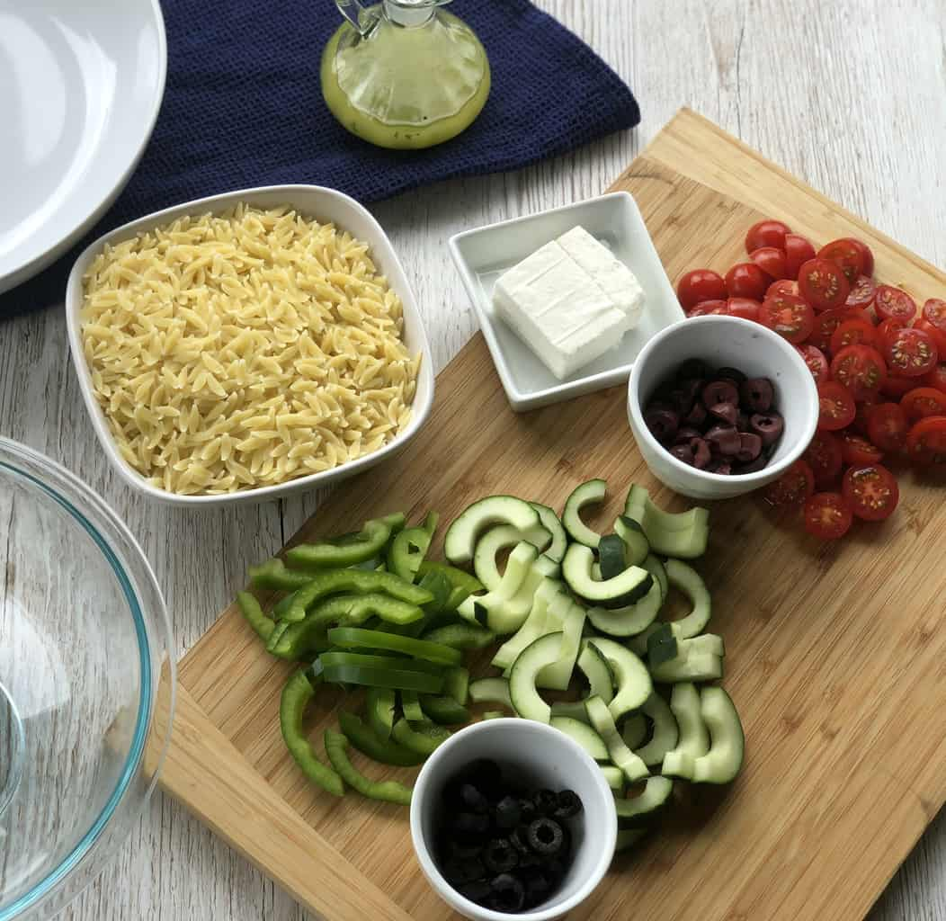 Prepared ingredients for the Greek Orzo Salad, sliced vegetables, dressing and pre cooked orzo pasta.