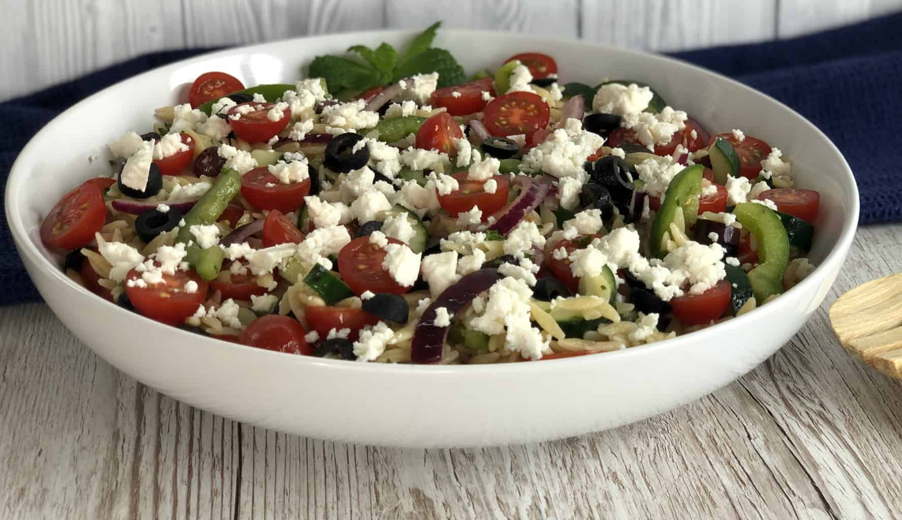 A large white bowl with greek orzo salad