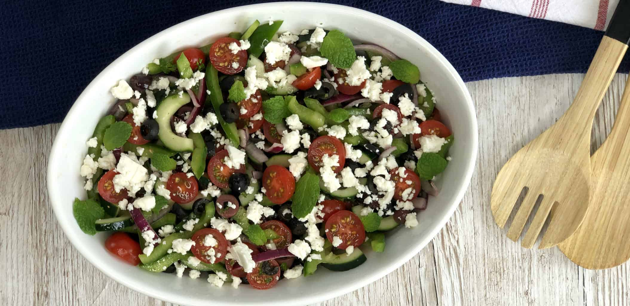 Overhead photo of a greek salad in a white bowl