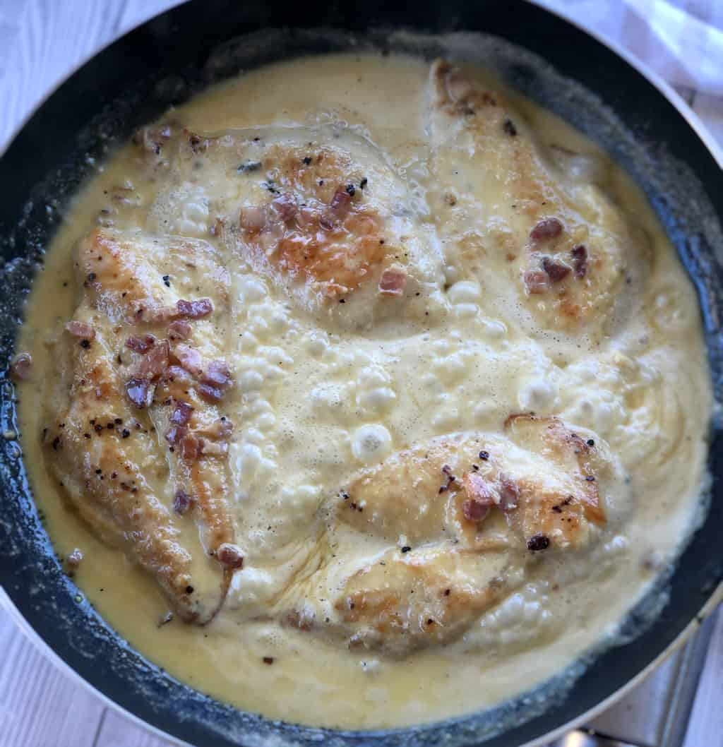 Chicken simmering in creamy bacon garlic sauce