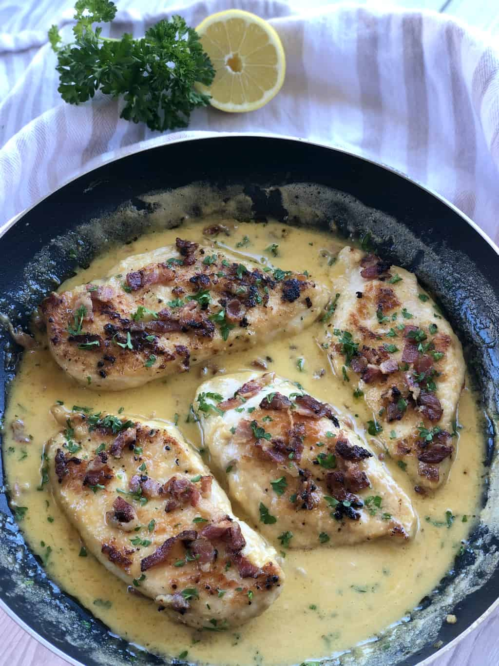 Creamy Chicken dish in a frying pan showing lemon and parsley as garnish