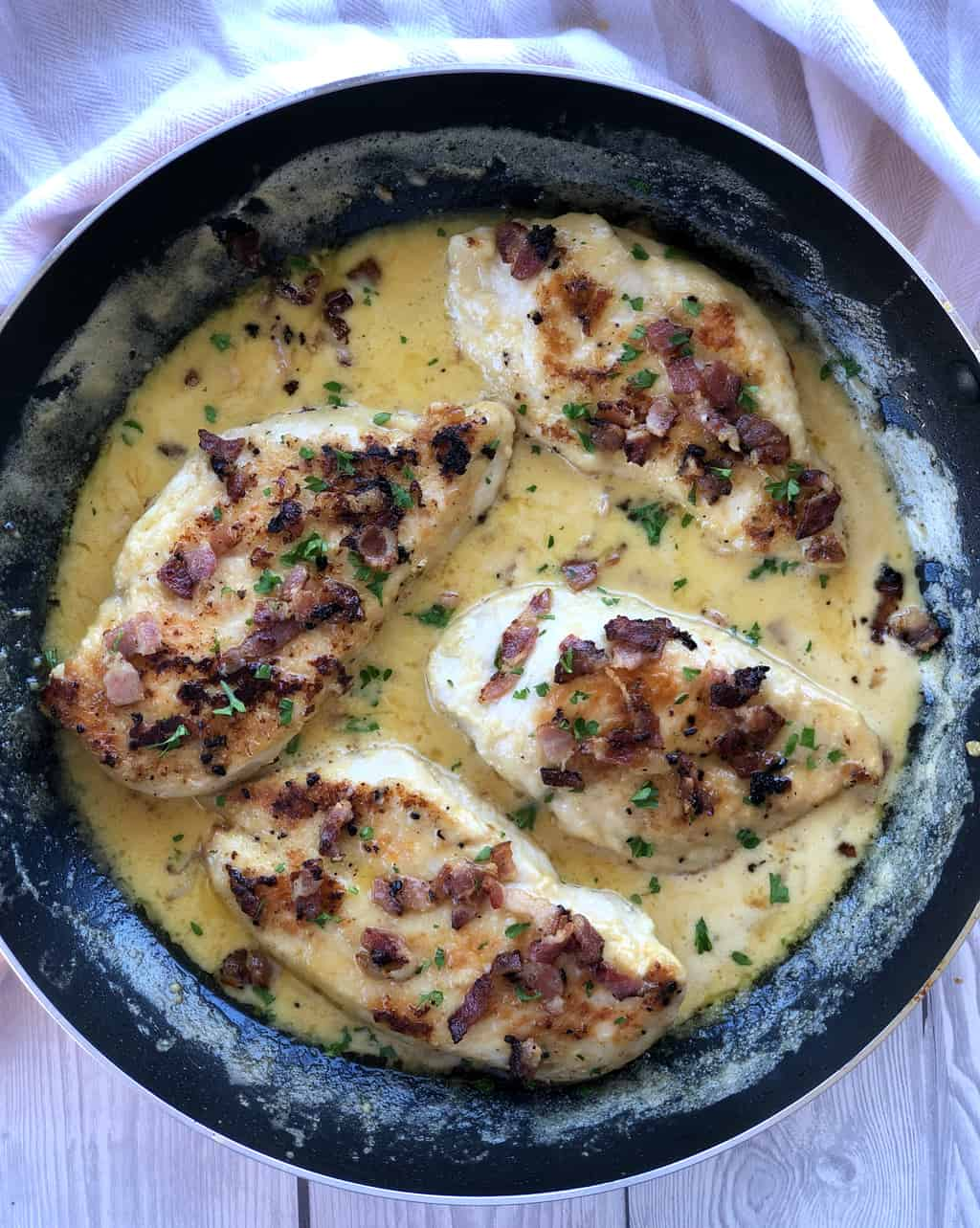Overhead photograph of four chicken breasts in a creamy sauce with bacon bits