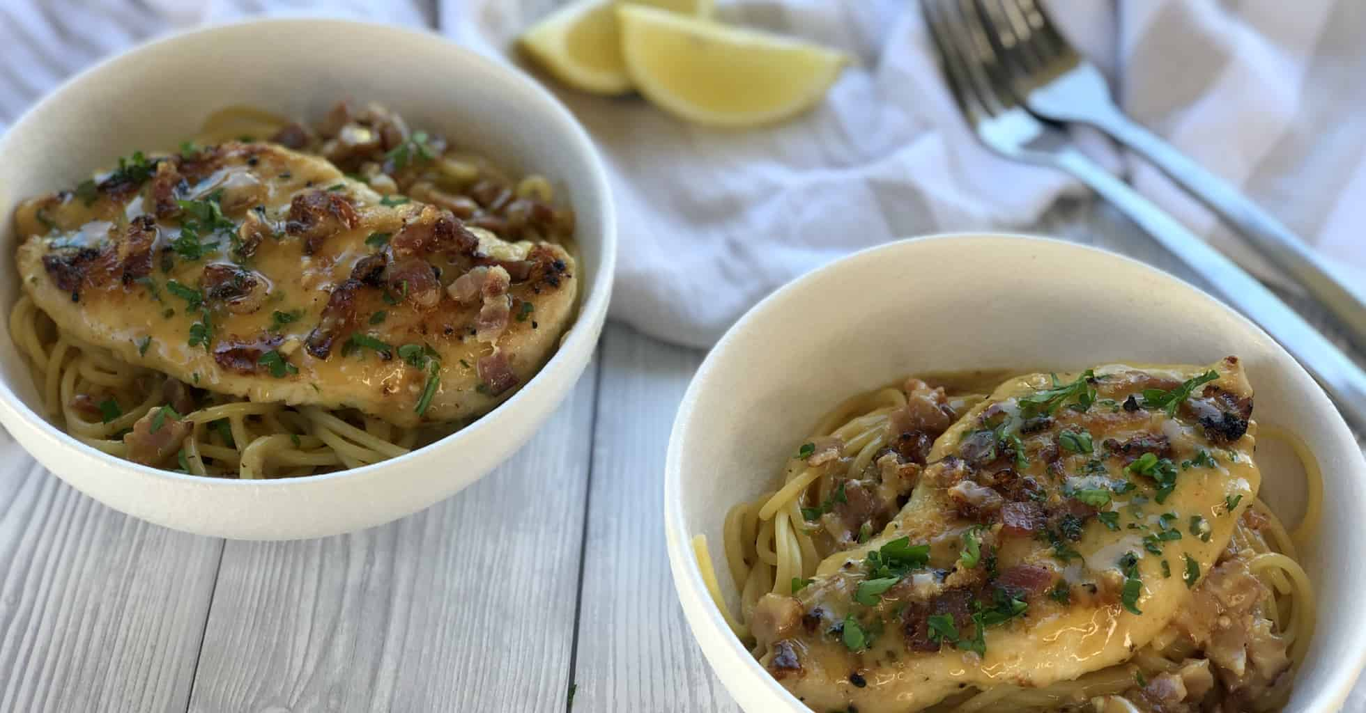 Two bowls of noodles with a chicken breast placed on top and creamy sauce
