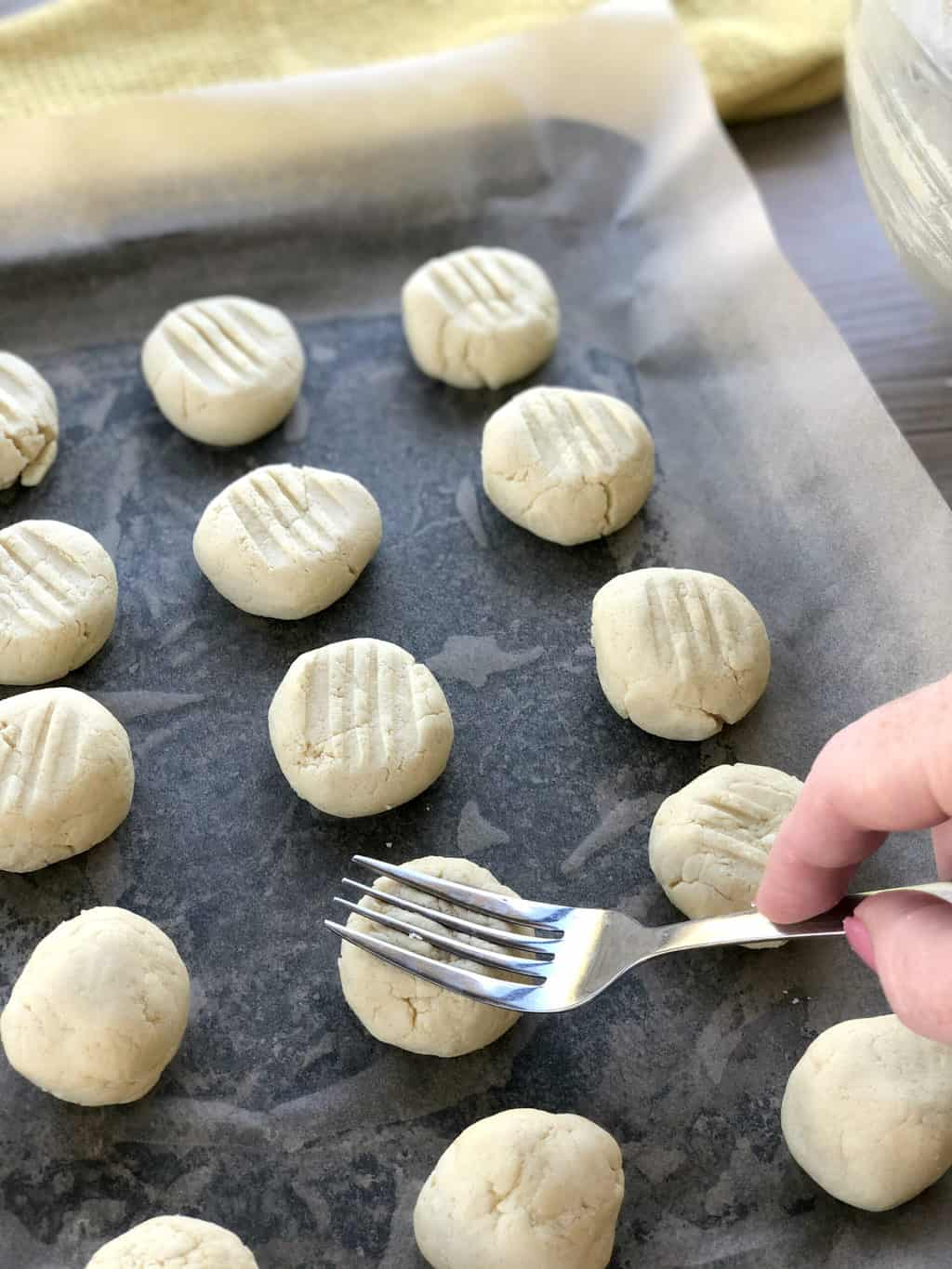 Pressing a fork into the top of the rounds of biscuit dough to make a pretty pattern