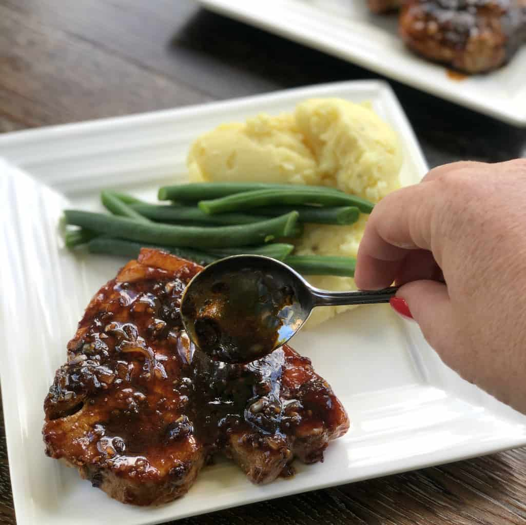Spooning an apricot and soy glaze over a pork chop on a white plate with side dishes