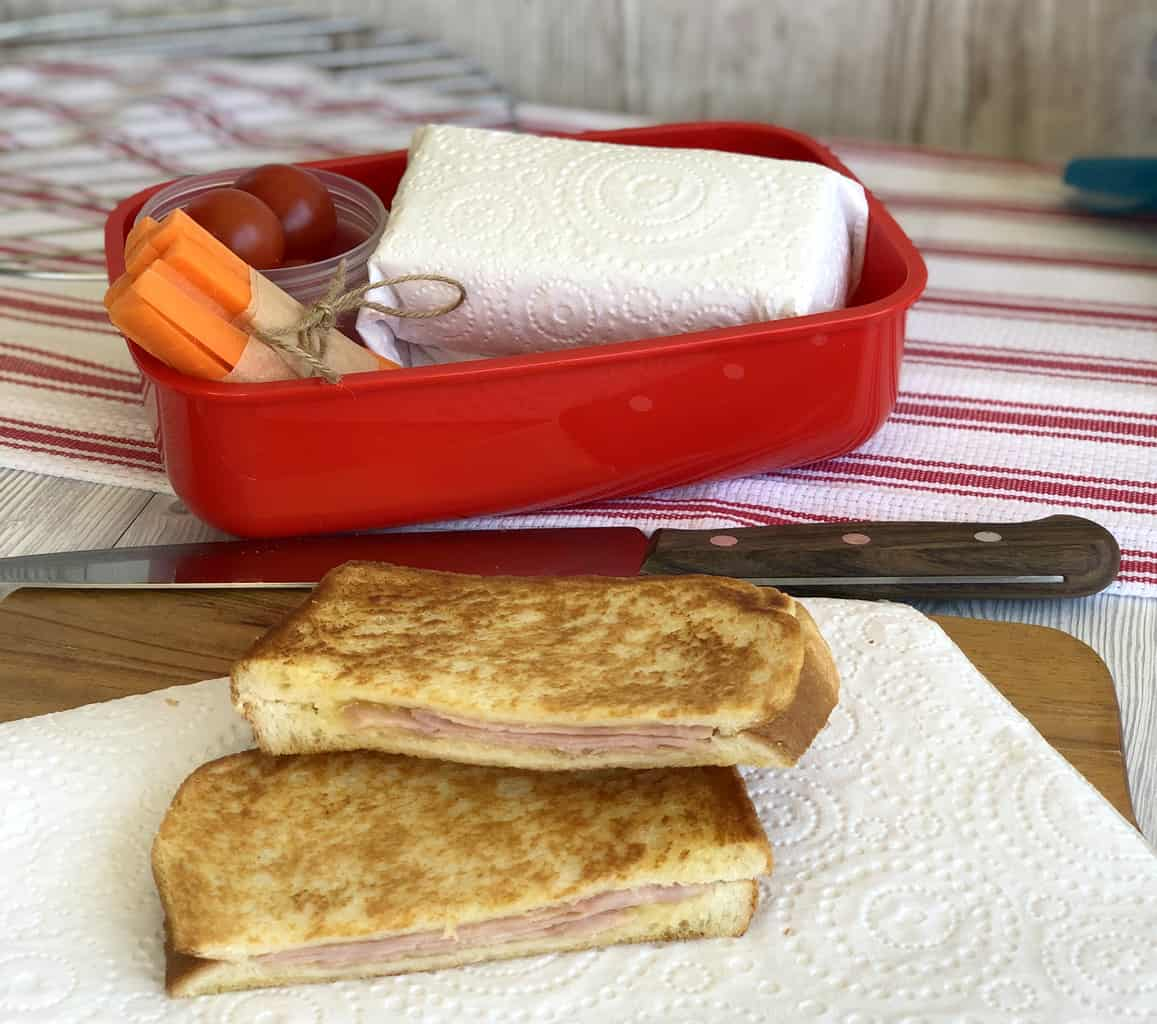Cooled toasted sandwiches and a lunch box with wrapped sandwich and vegetables.