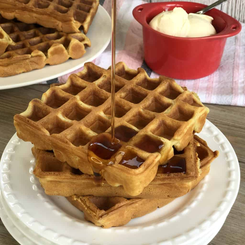 Plate of waffles with maple syrup pouring onto it and a bowl of cream