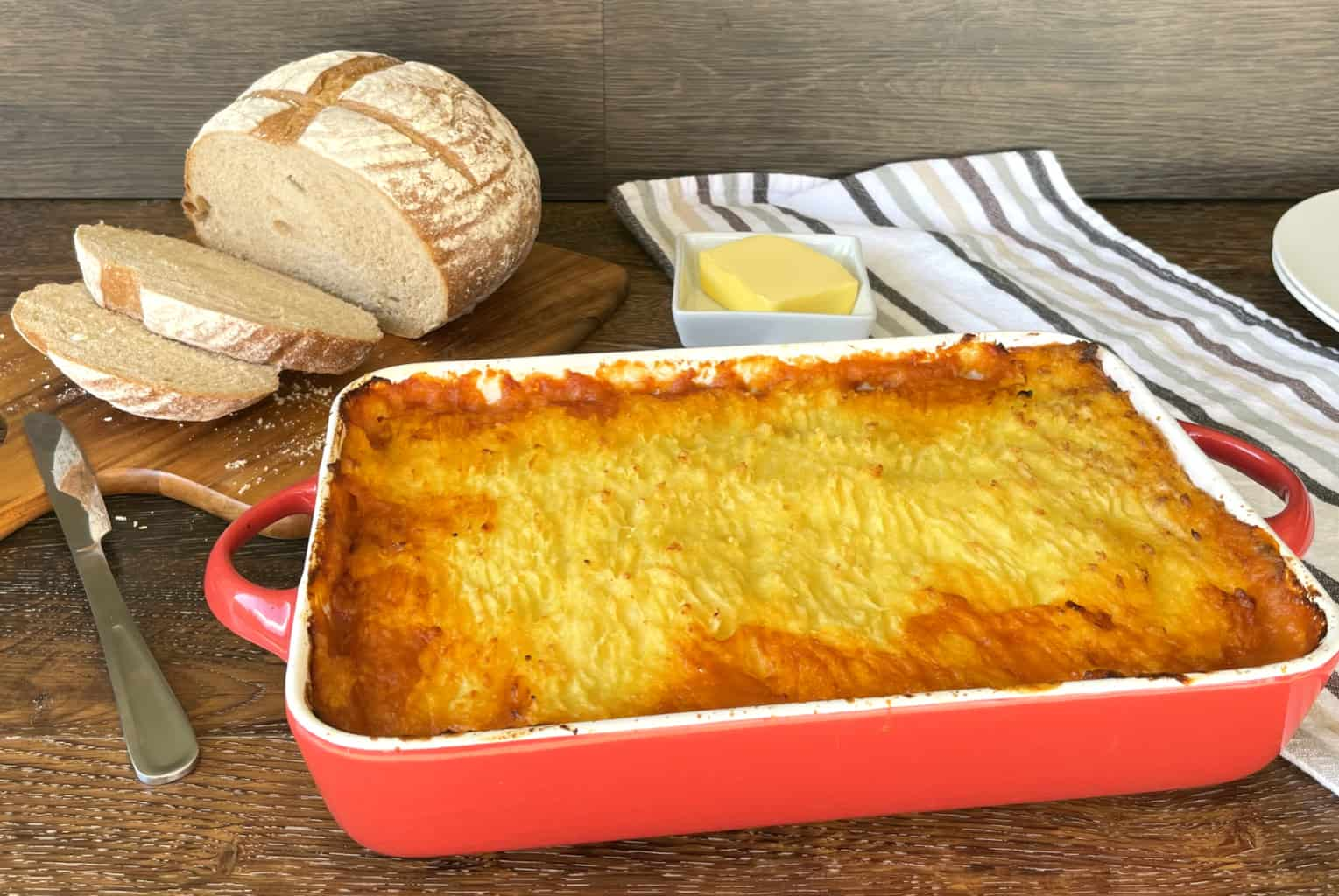 Large red dish with devilled sausage shepherds pie, crusty loaf of bread and butter