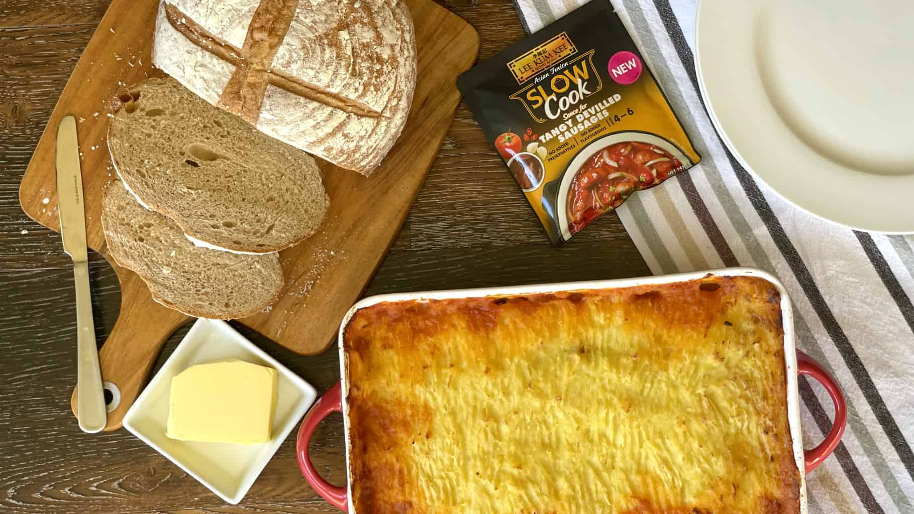 Overhead photograph of shepherds pie with loaf of bread and Lee Kum Kee Slow Cook Ready Sauce