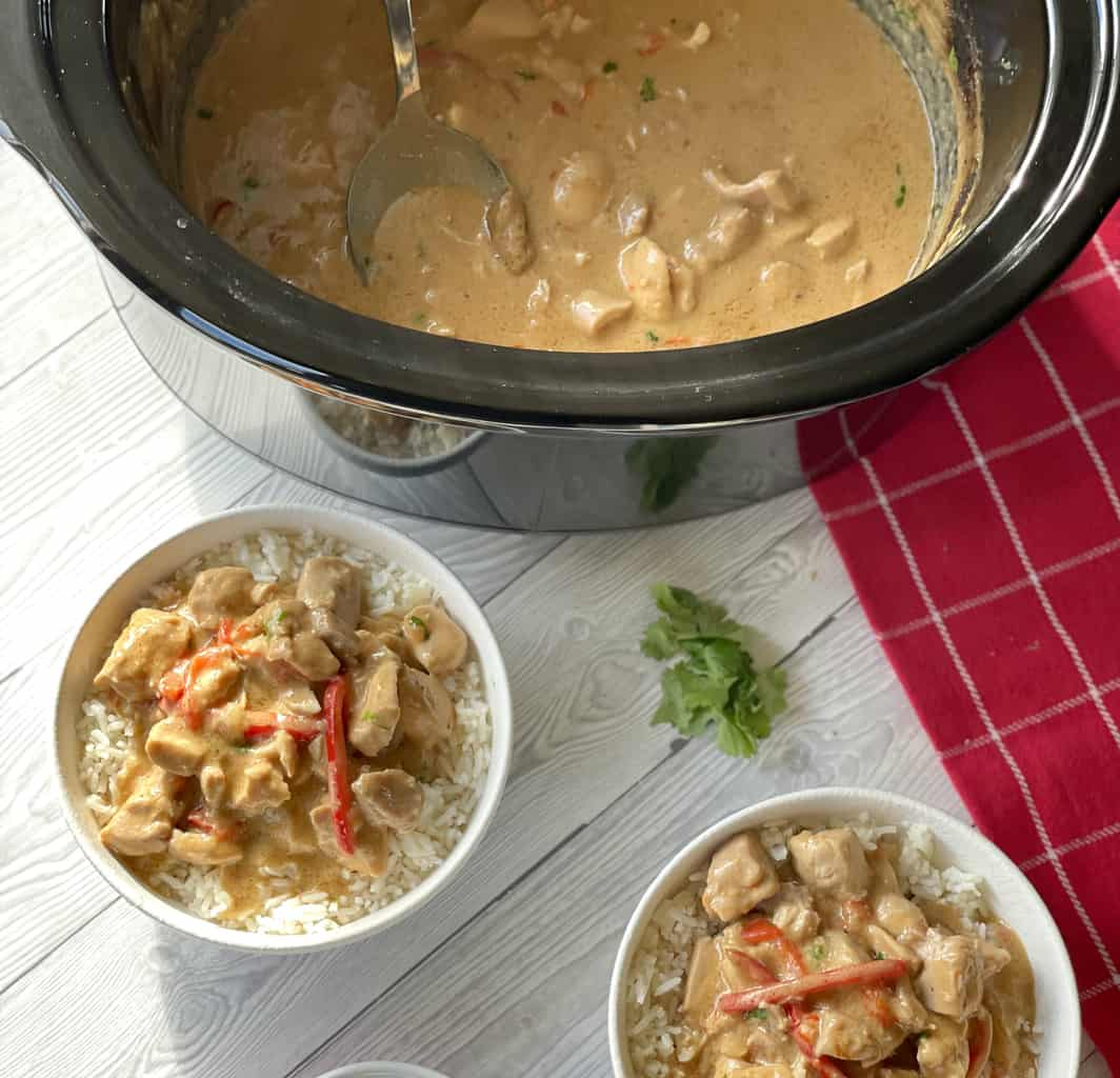 Slow Cooker with satay chicken, and two bowls of white rice with servings of the satay chicken