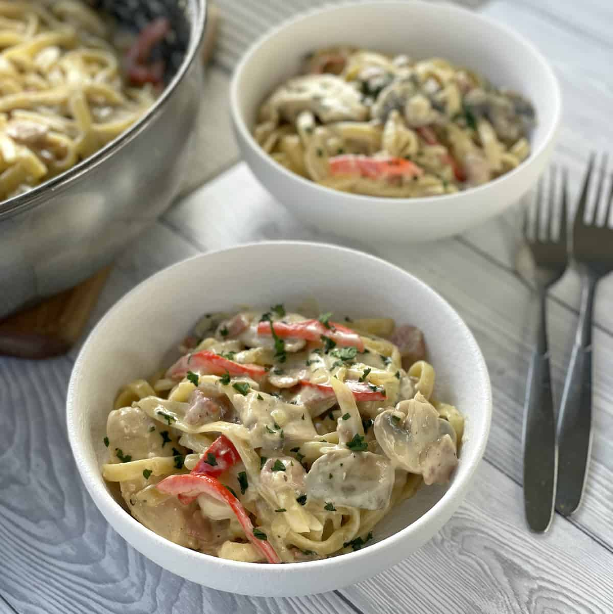 Two bowls of creamy bacon and chicken fettucine