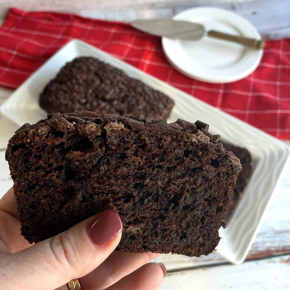 A hand holding a slice of double chocolate banana loaf