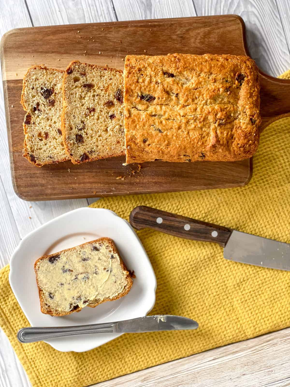 Overhead photograph of a sliced date and banana loaf and a piece with butter