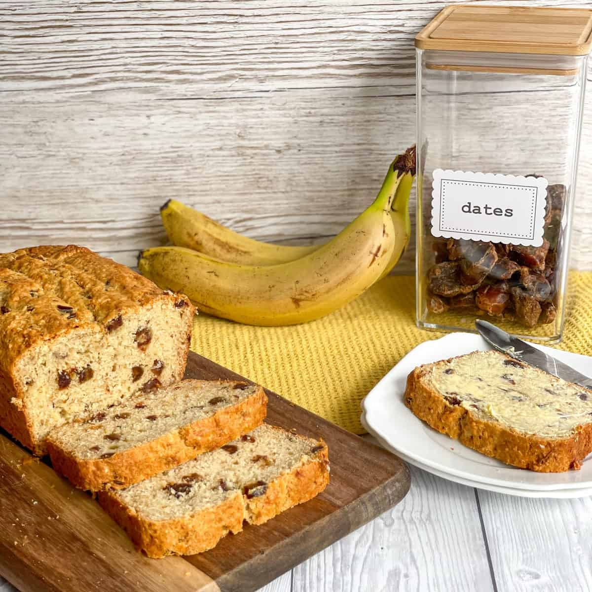 Container of Dates and fresh bananas next to a freshly baked loaf of banana and date loaf