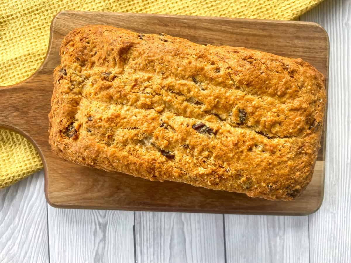 Freshly baked warm banana and date loaf on a wooden board with a yellow cloth