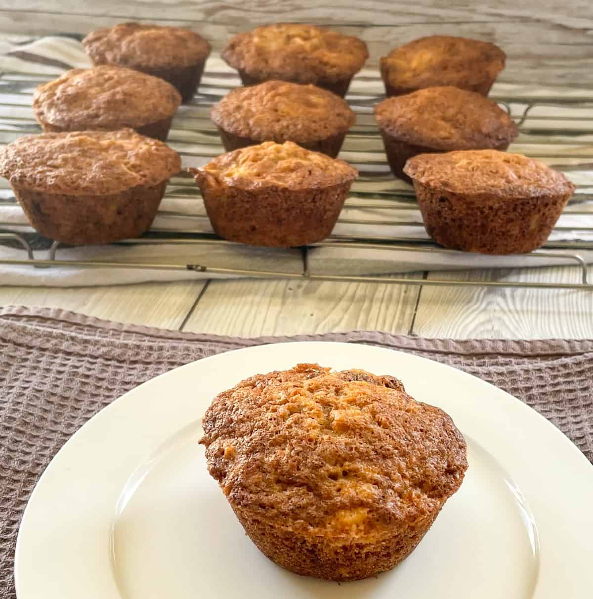 Muffins cooling on a wire rack and a plate with a single warm muffin