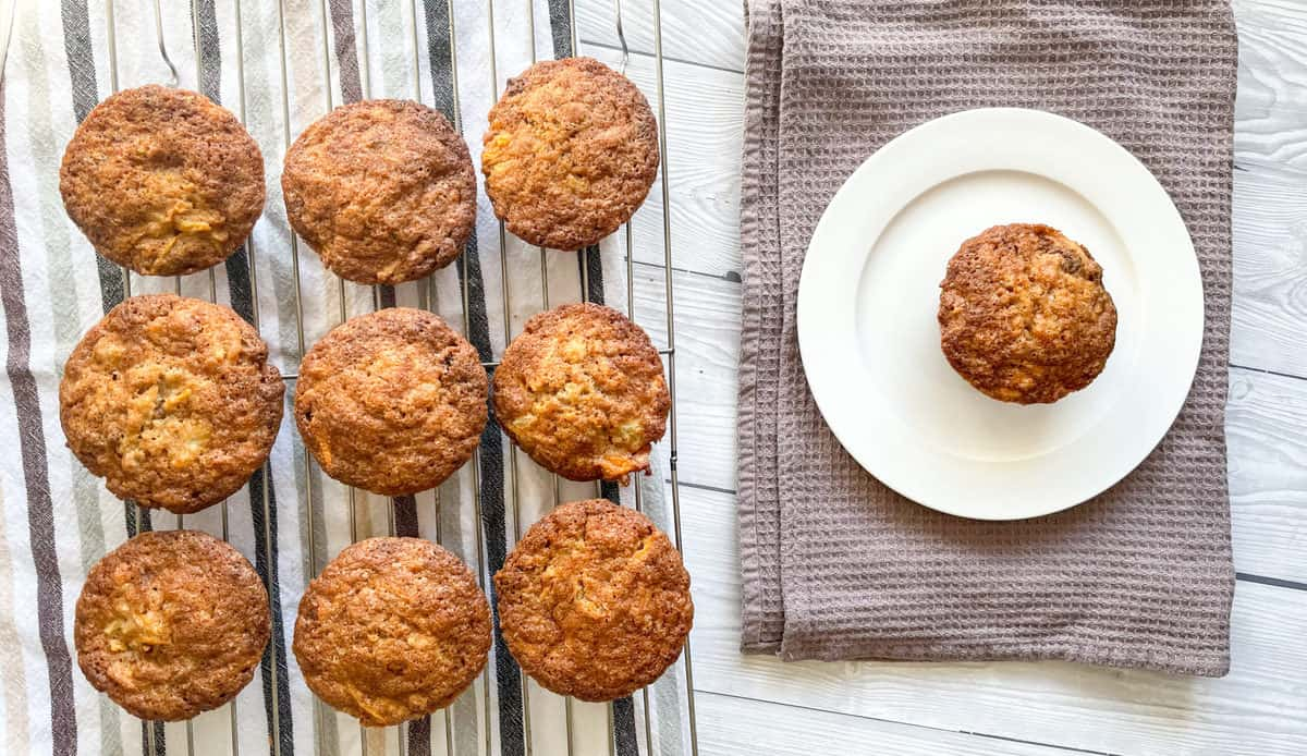 overhead photo of warm muffins on a wire rack and a white plate with a single carrot pineapple muffin