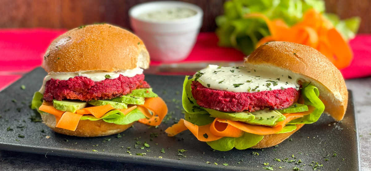 Fresh delicious burgers with beetroot patties, whipped feta and vegetables on a black plate