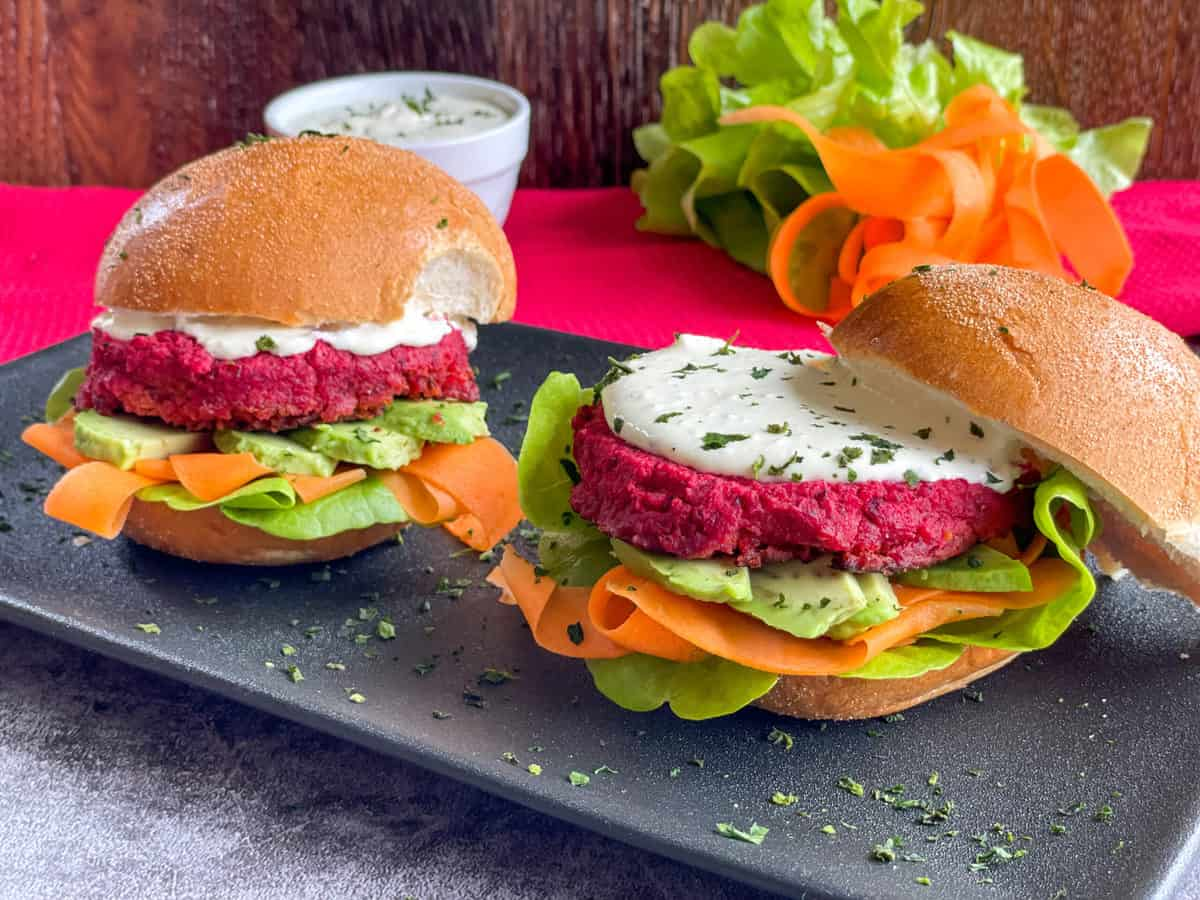 Beetroot burger patties on toasted buns with green and orange salad vegetables on a black plate