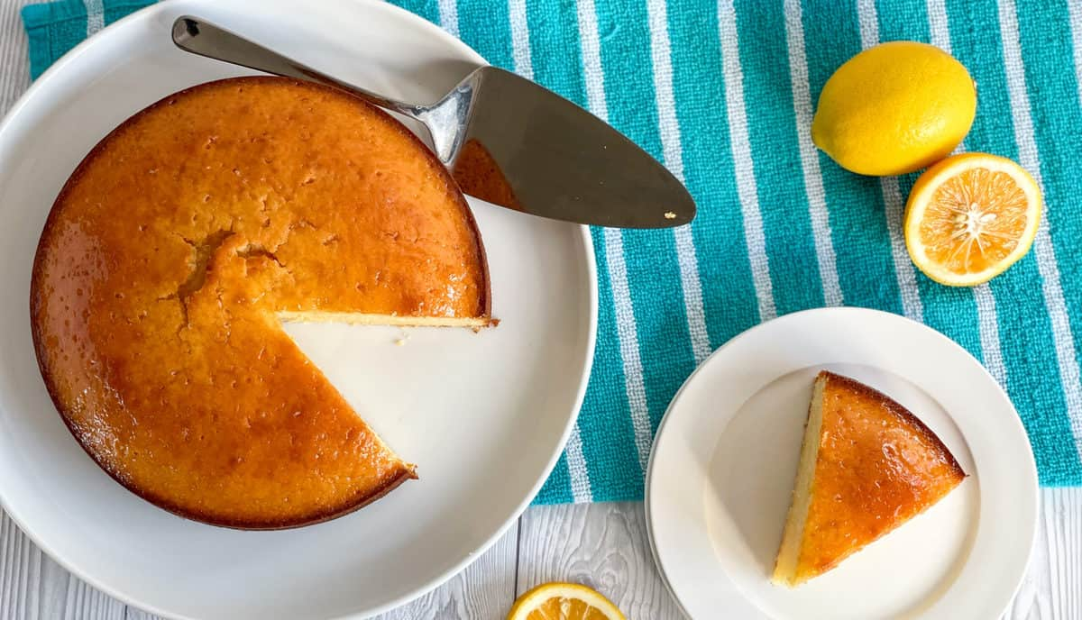overhead photo of a lemon syrup cake with a slice separated onto a white plate