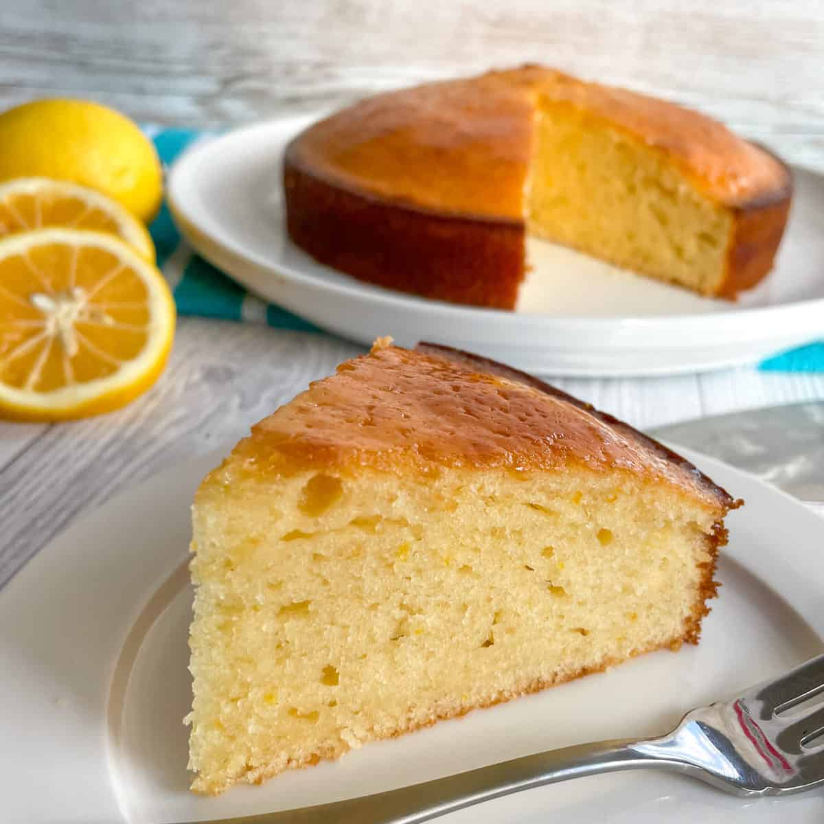 Slice of lemon syrup cake on a white plate, with the rest of the cake in the background